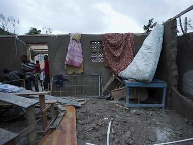 Residents walk into a destroyed home after it was damaged by Hurricane Matthew in Saint-Louis, Haiti. AP