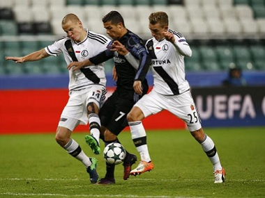 Real Madrid's Cristiano Ronaldo tussles for the ball with Leiga Warsaw players. Reuters