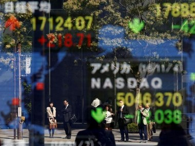 People are reflected in a display showing the Nikkei average (top in L) and the NASDAQ average of the U.S outside a brokerage in Tokyo, Japan, November 7, 2016. Reuters