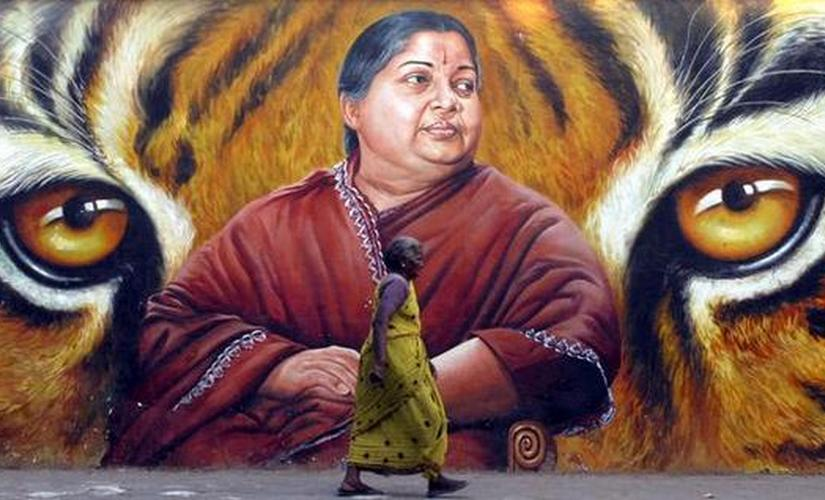 A woman walks in front of a portrait of Jayalalithaa. Reuters