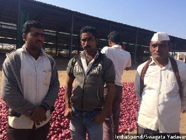 Onion farmer Deepak Patil (centre) has a bank account, a cell phone, and accepts payments in cheque. Patil could, in theory, move to cashless transactions, but in reality there is no Internet access where he lives. Image courtesy: IndiaSpend