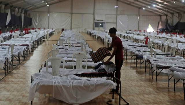 A worker prepares a bed inside a makeshift quarantine facility for COVID-19 patients in Mumbai. AP