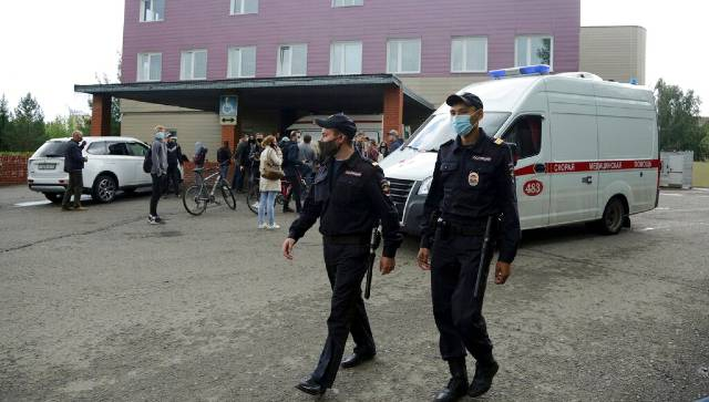 Police patrol the area as journalists gather at the hospital where Alexei Navalny was hospitalized in Omsk, Russia. AP